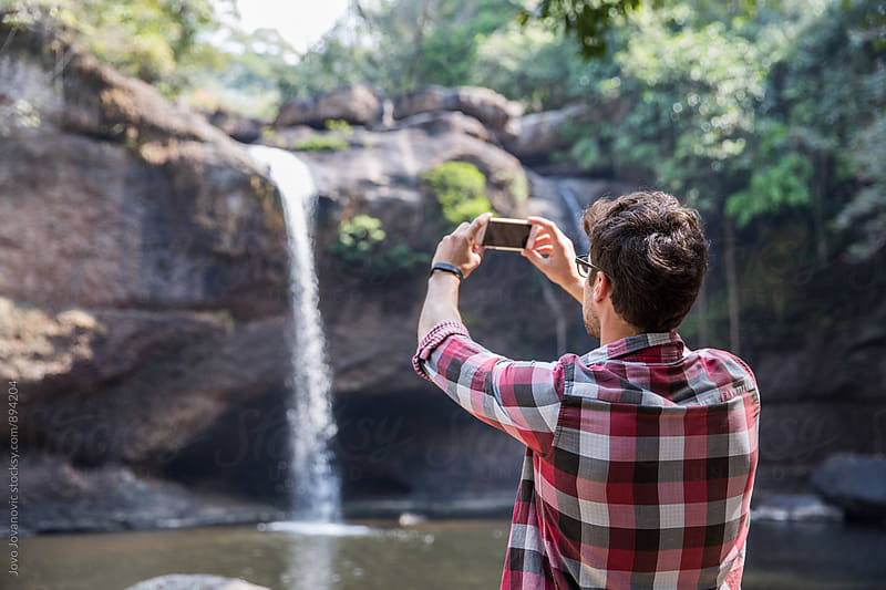 Man taking a photo of a waterfall by Jovo Jovanovic for Stocksy United