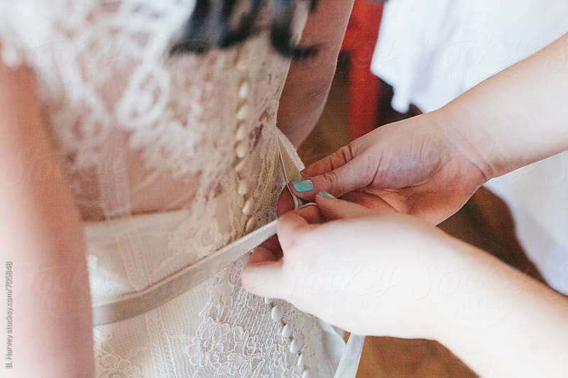 Helping a Bride into her Dress by B. Harvey for Stocksy United