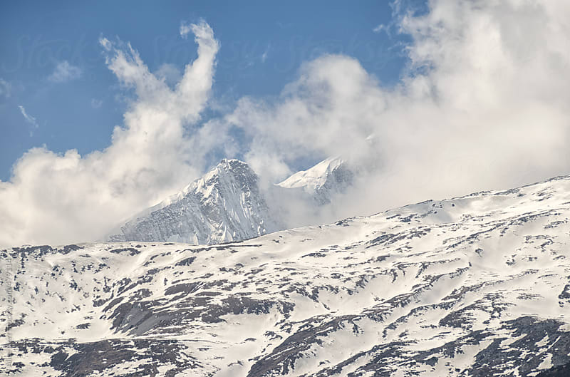 Clouds rising from snowy mountain peaks by Alice Nerr for Stocksy United