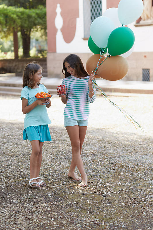 Two young girls with food and balloons for a party by Miquel Llonch for Stocksy United