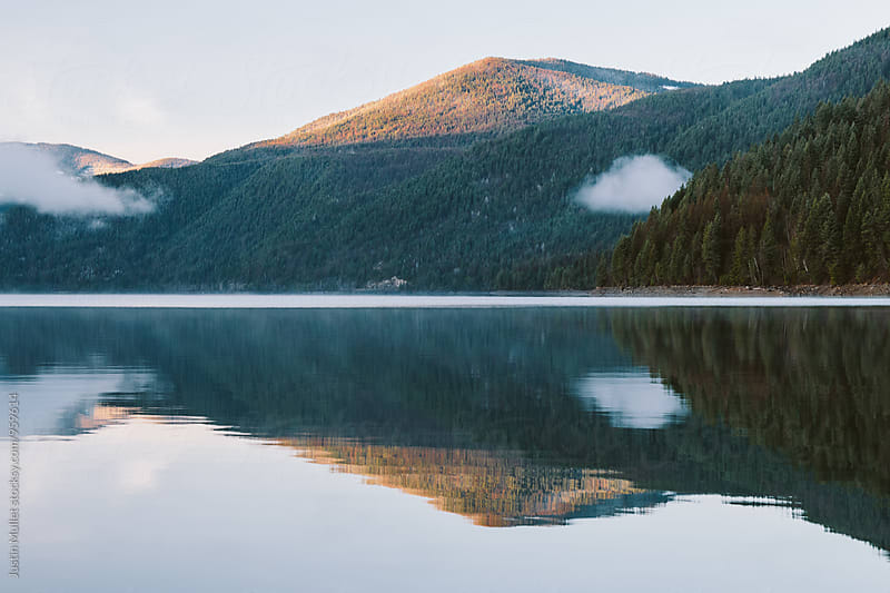 Perfect reflection of sunrise on mountain.  by Justin Mullet for Stocksy United