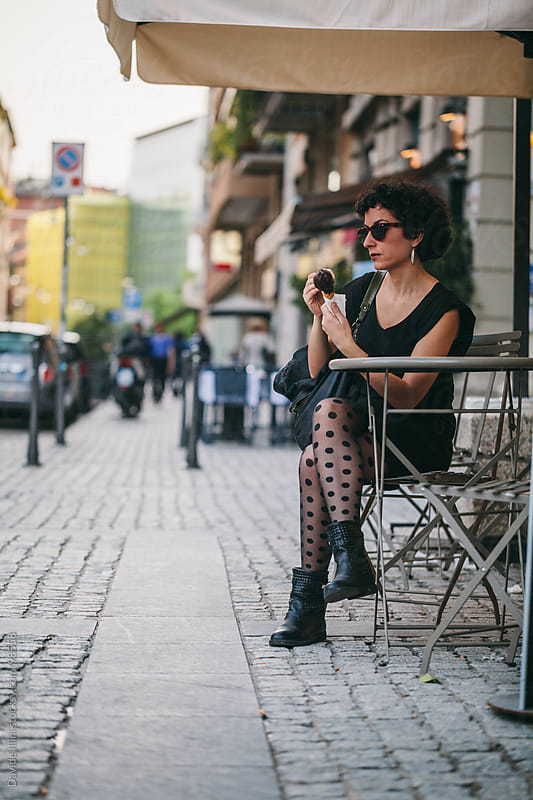 Young woman eating ice cream on the street by Davide Illini for Stocksy United