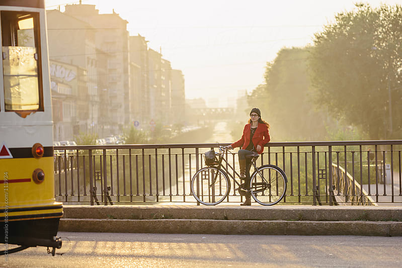Young woman resting on a bridge with her bicycle. by michela ravasio for Stocksy United