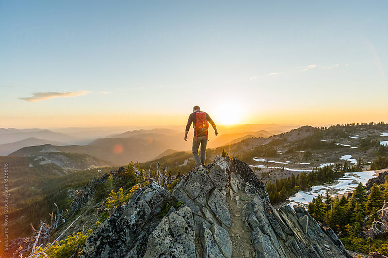 Man on top of mountain at sunset by Isaac Lane Koval for Stocksy United