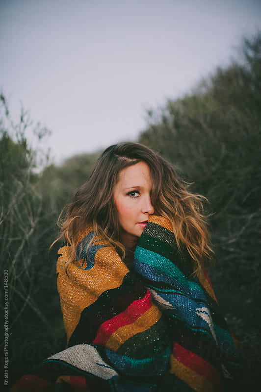 Pretty woman wrapped up in blanket at dusk by Kristin Rogers Photography for Stocksy United