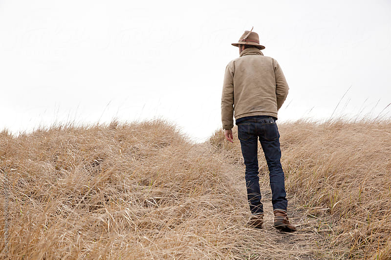 A Man In A Tan Colored Grass Setting On A Trail Hiking by Carey Haider for Stocksy United