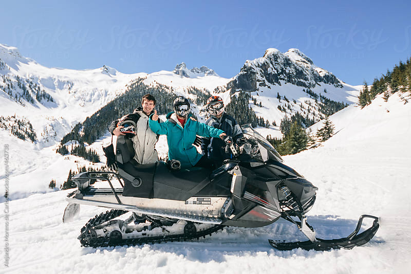 Group of friends with a snowmobile on snow mountain landscape by Alejandro Moreno de Carlos for Stocksy United
