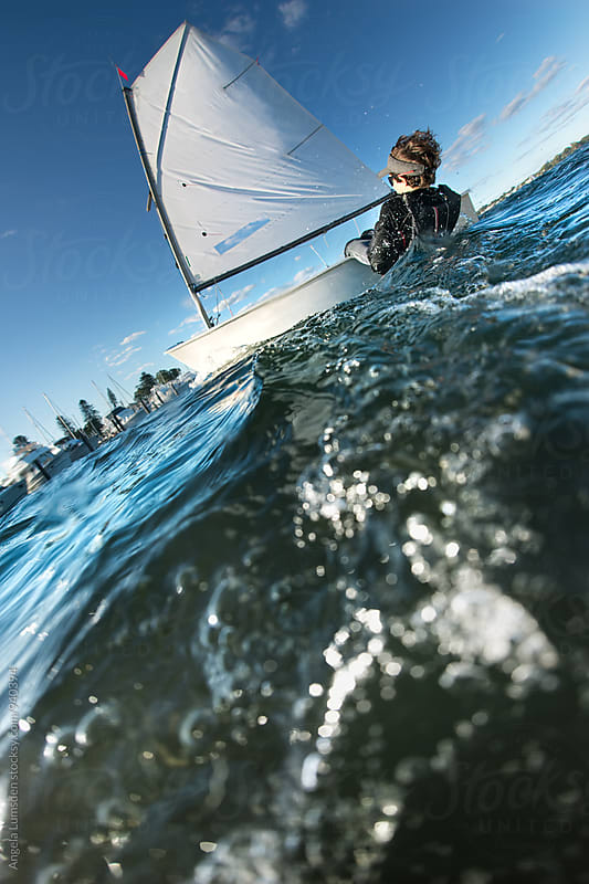 Action capture of a child sailing an optimist dinghy by Angela Lumsden for Stocksy United