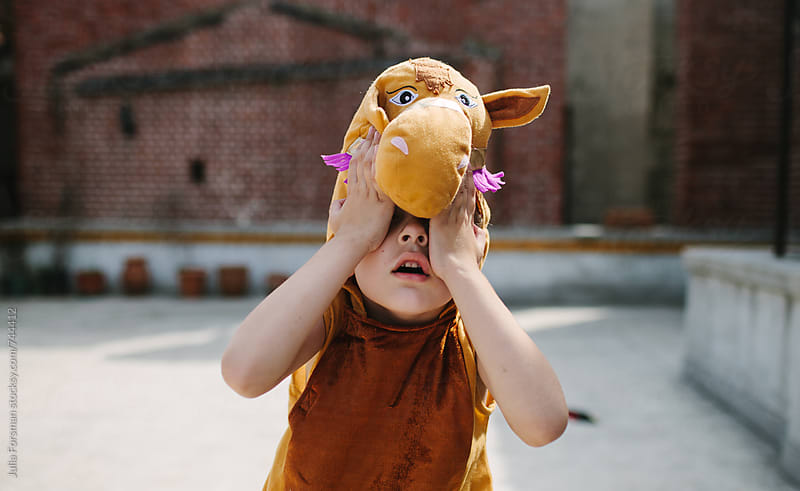 Young child wearing a camel costume covers his eyes with his hands. by Julia Forsman for Stocksy United