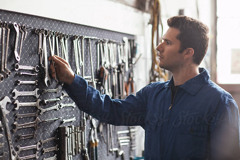 Mechanic Choosing Tools at His Workshop by Lumina for Stocksy United