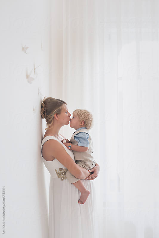 Gorgeous pregnant mother holding and kissing her cute son by Lea Csontos for Stocksy United