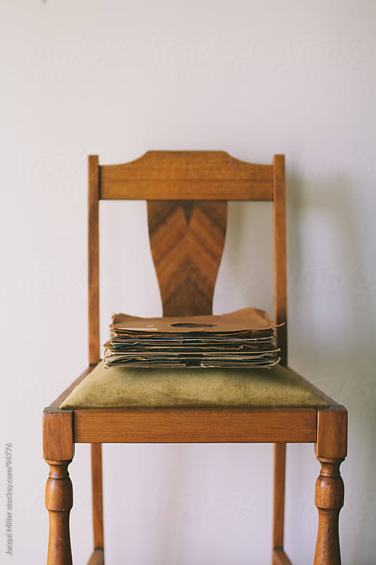 Pile of old records on an antique chair by Jacqui Miller for Stocksy United