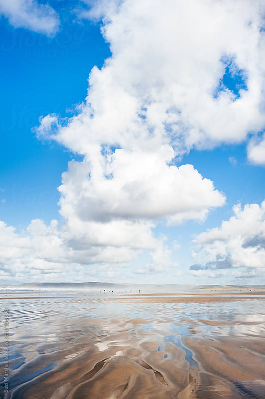 Clouds reflected in puddles on the beach by Suzi Marshall for Stocksy United