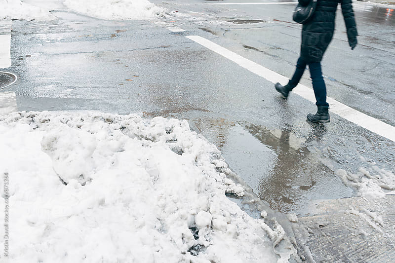 Snow and slush puddle on city street. New York City. by Kristin Duvall for Stocksy United