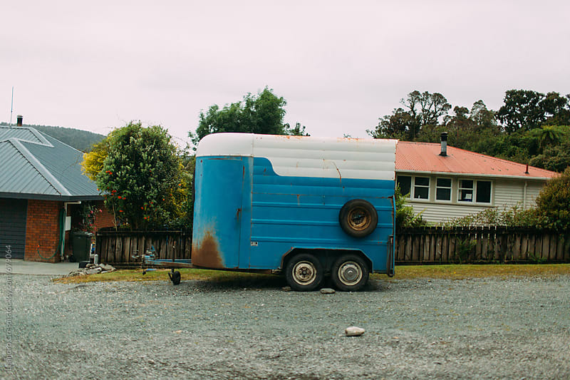 A horse trailer parked outside a house by Leandro Crespi for Stocksy United