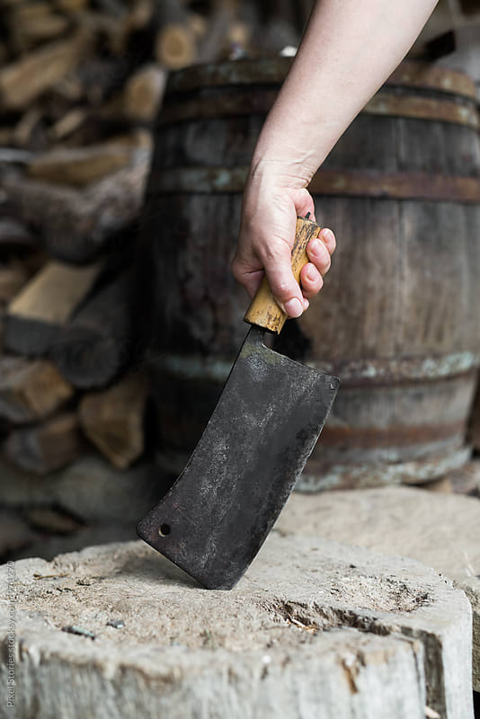 Hand holding old cleaver lodged in a trunk by Pixel Stories for Stocksy United