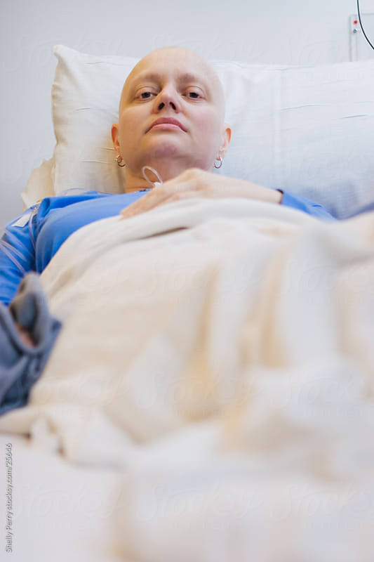 Somber woman at the hospital for a round of chemotherapy, cancer treatment by Shelly Perry for Stocksy United