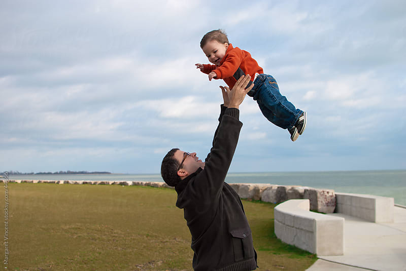 a father playfully tosses his son in the air by Margaret Vincent for Stocksy United