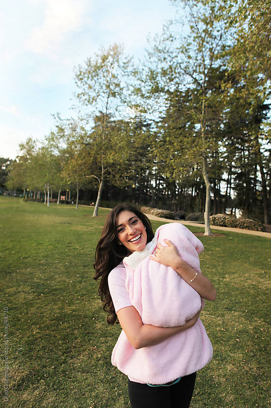 Long haired brunette woman in park smiling while holding baby in a pink blanket by Dina Giangregorio for Stocksy United