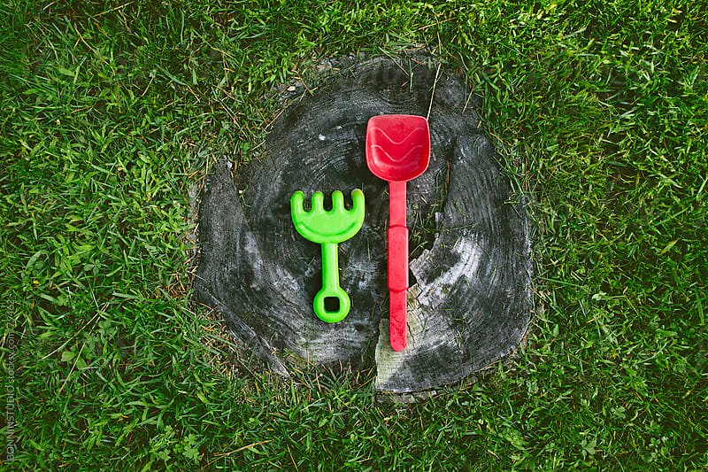 Pair of plastic shovel toys on the lawn. by BONNINSTUDIO for Stocksy United