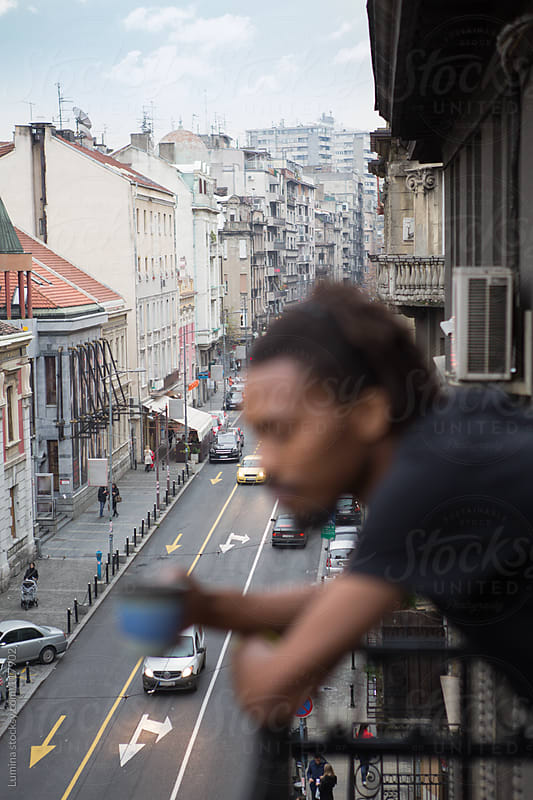 African Man Drinking Tea on the Balcony by Lumina for Stocksy United