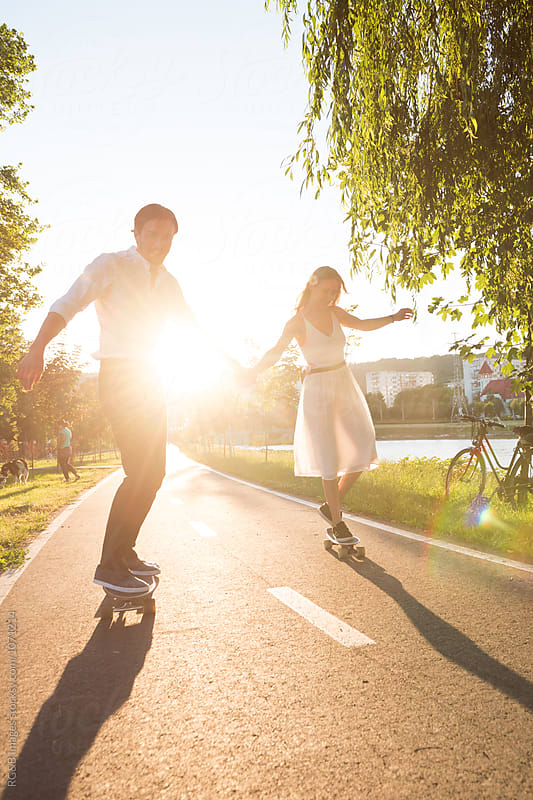 Young couple having fun activities together riding skateboards by RG&B Images for Stocksy United