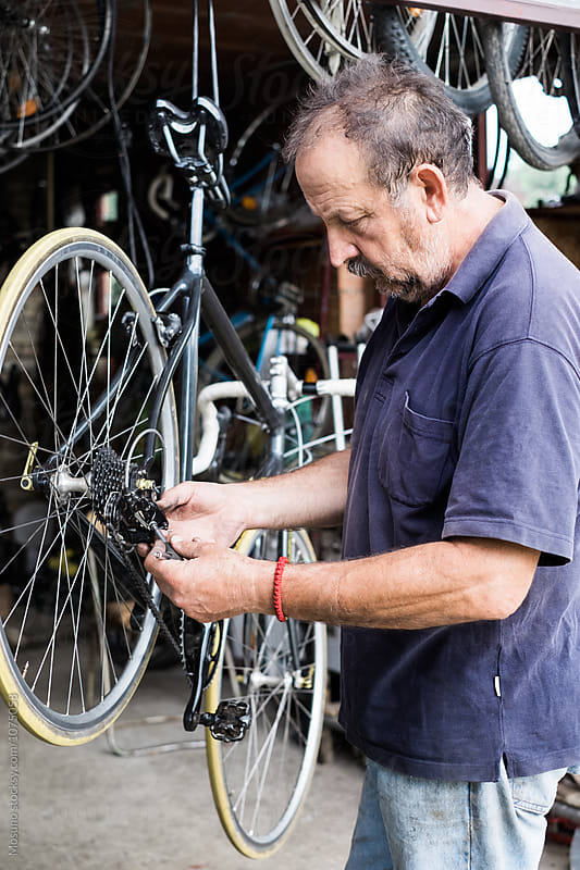Man Repairing Bicycle Chain  by Mosuno for Stocksy United
