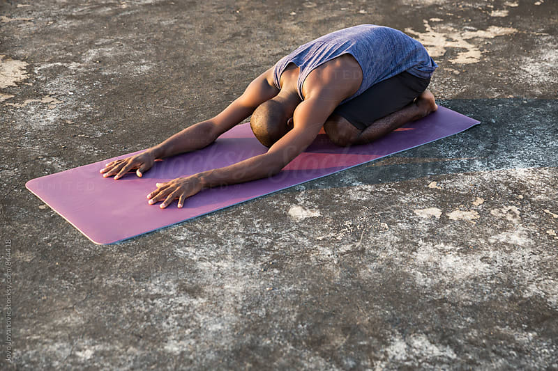 Fit dark skinned man stretching his back during a yoga practice outdoors  by Jovo Jovanovic for Stocksy United