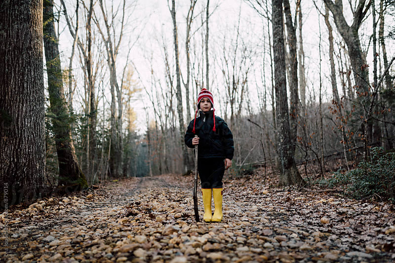 child standing on a rocky path in forest by Léa Jones for Stocksy United