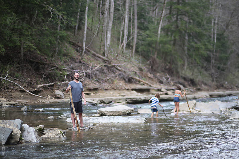 A Man And His Children Hiking Through A River Bed by ALICIA BOCK for Stocksy United