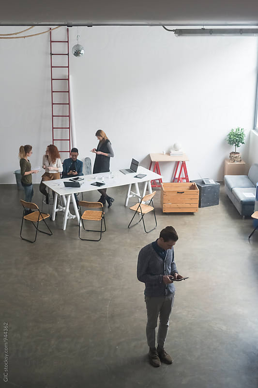 Young business people meeting in a modern workspace  by Simone Becchetti for Stocksy United