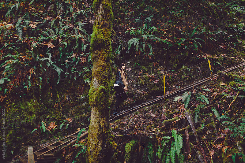 A girl climbing stairs in the forest by Ania Boniecka for Stocksy United