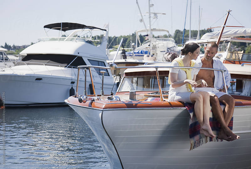 Couple sitting on yacht deck by Andersen Ross Photography for Stocksy United