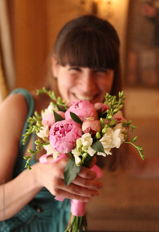 A smiling young woman holds a bouquet.  by Amos Chapple for Stocksy United