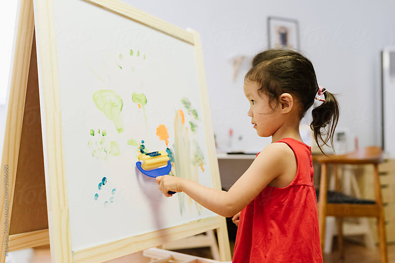 Cute little girl painting at home using an easel stand by MaaHoo Studio for Stocksy United