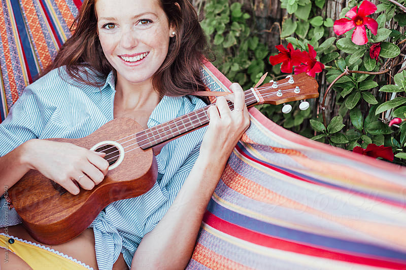 Young woman playing ukulele in a hammock by Vera Lair for Stocksy United