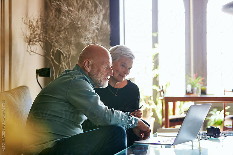 Senior Couple Using Laptop In Living Room by ALTO IMAGES for Stocksy United
