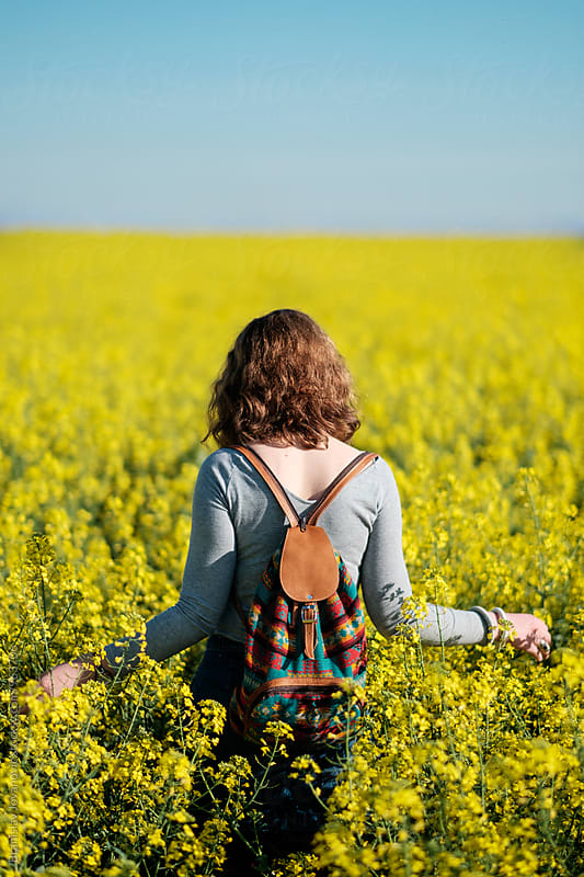 Woman with Backpack Walking Through the Field of Yellow Flowers by Branislav Jovanović for Stocksy United