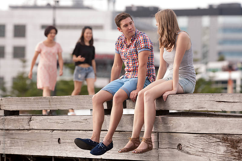 Casual young people sitting on a pier by Ben Ryan for Stocksy United