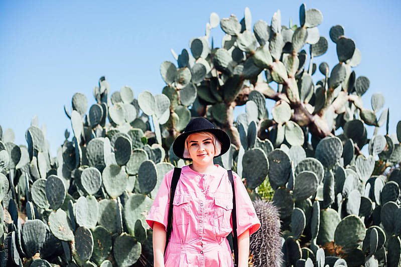 Young woman in sunny Cactus Garden by Kara Riley for Stocksy United