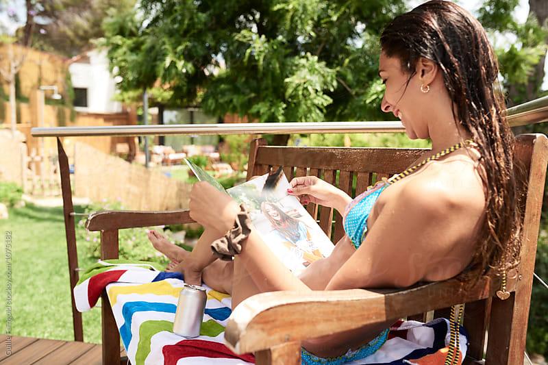 Smiling wet-haired brunette in bikini reading magazine on balconysummer reading by Guille Faingold for Stocksy United