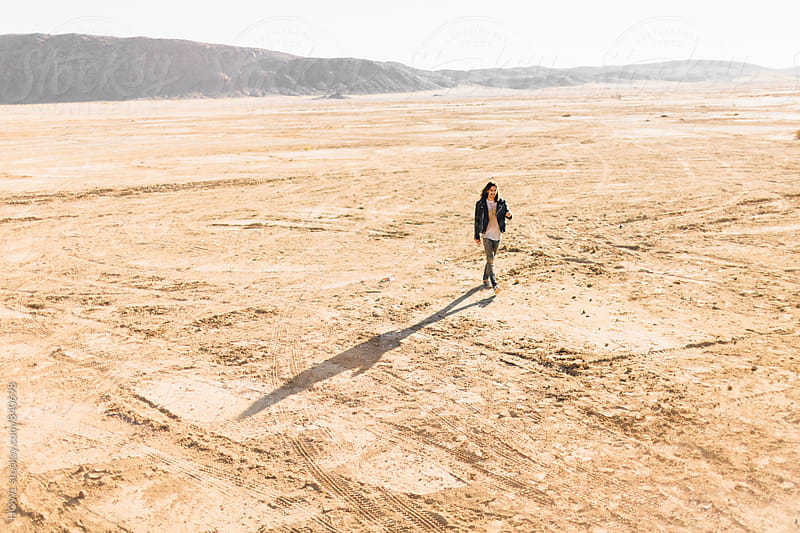 A young man walks alone in the vast Californian desert  by HOWL for Stocksy United