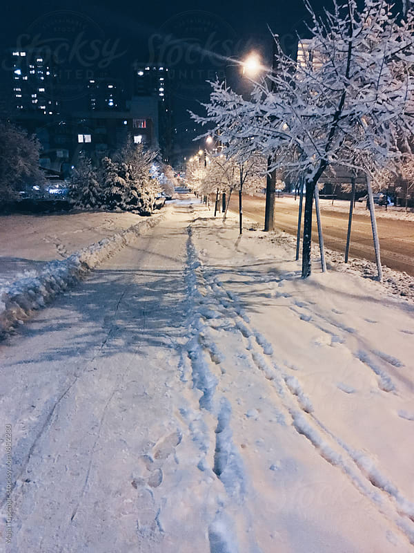 Beautiful streets covered in snow at night by Maja Topcagic for Stocksy United