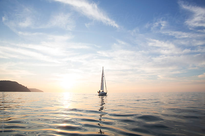 Sailing boat at sunset. by Hugh Sitton for Stocksy United