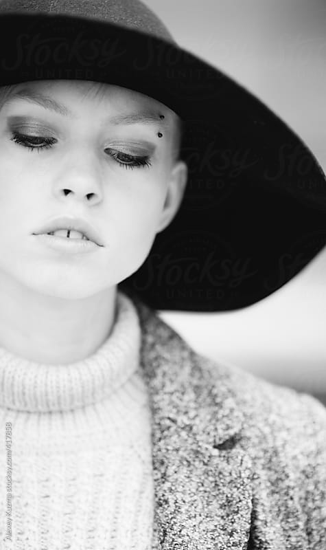 close up of young woman with black hat by Alexey Kuzma for Stocksy United