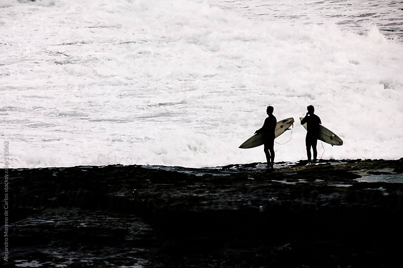 Surfers silhouettes on the coast with waves breaking by Alejandro Moreno de Carlos for Stocksy United