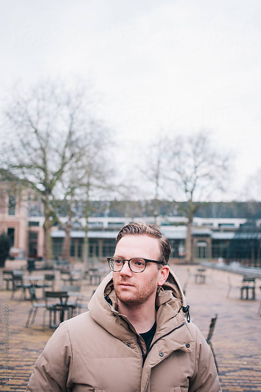 Young man with glasses standing on a square on a winter or autumn day by Ivo de Bruijn for Stocksy United