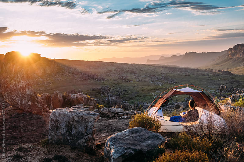 Woman sitting in her tent watching the sunset over a mountainous valley by Micky Wiswedel for Stocksy United