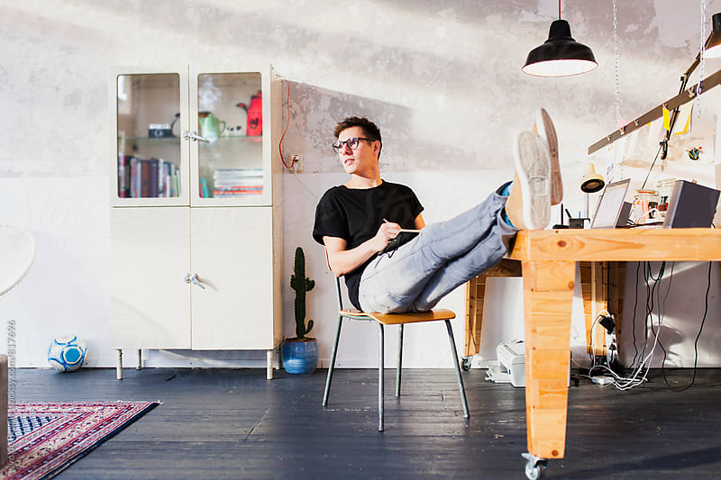 Entrepreneur or professional working behind his laptop with his legs on his desk by Ivo de Bruijn for Stocksy United