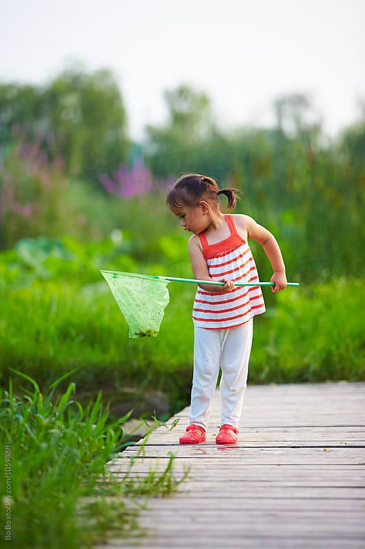 lovely little asian girl holding net outdoor by Bo Bo for Stocksy United
